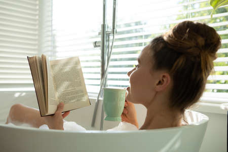 A Caucasian woman spending time at home, having a foamy bath, reading a book, drinking. Lifestyle at home isolating, social distancing in quarantine lockdown during coronavirus covid 19 pandemic.
