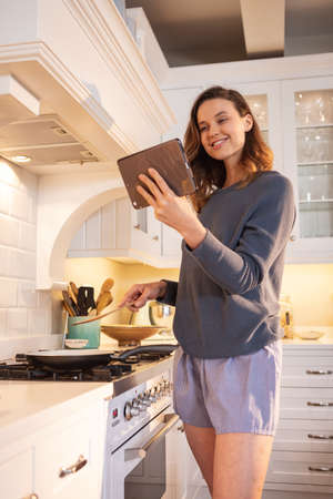 Caucasian woman spending time at home, cooking in the kitchen, using her tablet. Lifestyle at home isolating, social distancing in quarantine lockdown during coronavirus covid 19 pandemic.