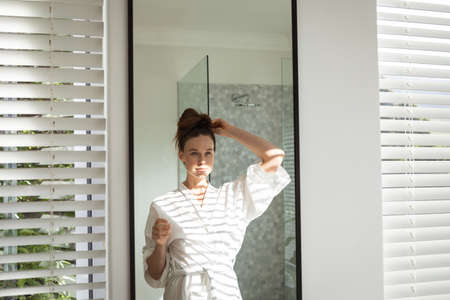 A Caucasian woman spending time at home, tying her hair, looking in the mirror. Lifestyle at home isolating, social distancing in quarantine lockdown during coronavirus covid 19 pandemic.