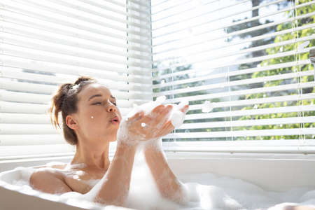 A Caucasian woman spending time at home, blowing foam, having bath. Lifestyle at home isolating, social distancing in quarantine lockdown during coronavirus covid 19 pandemic. Standard-Bild