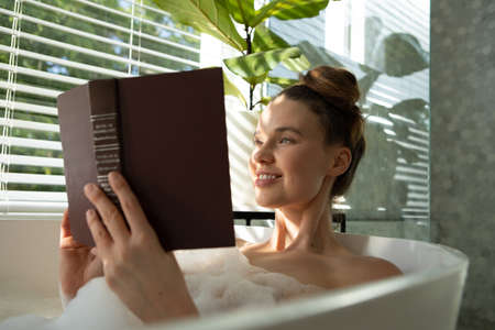 A Caucasian woman spending time at home, having a foamy bath, reading a book. Lifestyle at home isolating, social distancing in quarantine lockdown during coronavirus covid 19 pandemic.