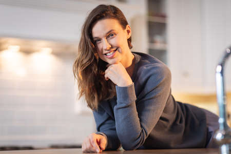 Portrait of a Caucasian woman spending time at home, sitting in the kitchen, smiling. Lifestyle at home isolating, social distancing in quarantine lockdown during coronavirus covid 19 pandemic.