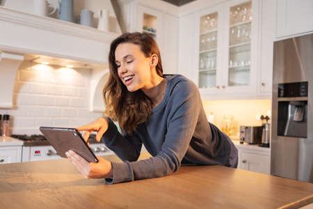Caucasian woman spending time at home, sitting in the kitchen, using her tablet. Lifestyle at home isolating, social distancing in quarantine lockdown during coronavirus covid 19 pandemic.