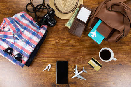Top view of a variety of essential travelling items with black smartphone and camera, arranged on a textured wooden table.