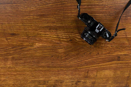 Close up top view of a black digital SLR camera arranged on a textured wooden surface