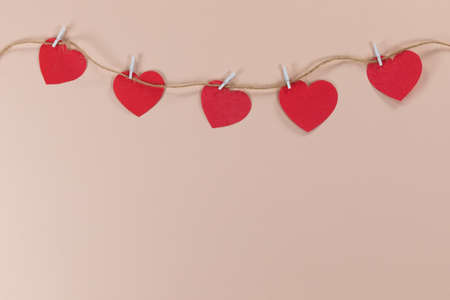 Close up view of five red hearts cut from paper and held by small clothe pegs on a piece of cord, arranged on a plain pink background. 版權商用圖片