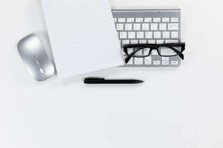 Close up top view of an empty page in a notebook, a pen, a keyboard, a computer mouse and glasses arranged on a plain white background
