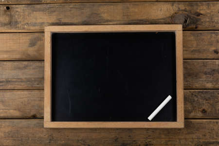 Top view of a composition with a black chalkboard and a piece of white chalk, arranged on a textured wooden surface.