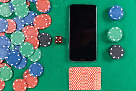 Close up top view of a black smartphone, playing cards, a red dice and gambling chips, arranged on a plain green surface.