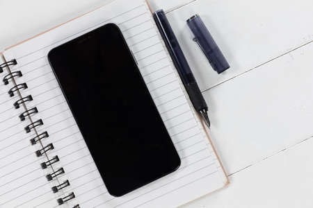 Close up top view of a black smartphone, a notebook and a black pen arranged on a plain white background