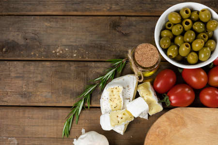 Top view of a wooden cutting board with a bowl of green olives, some cheese, cherry tomatoes and a spring of fresh thyme, arranged on a on a textured wooden surface.