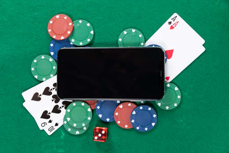 Close up top view of a black smartphone, playing cards, a red dice and colorful gambling chips, arranged on a plain green surface.