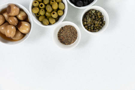 Top view of a six bowls with fresh olives, nuts and seasoning, arranged on a on a plain white surface.