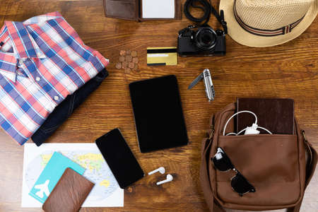 Top view of a variety of essential travelling items with tablet, smartphone and camera, arranged on a textured wooden table.