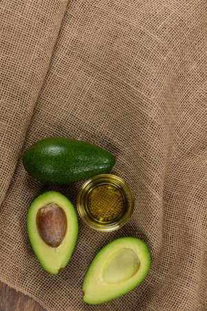Top view of an avocado and a halved avocado with a bowl of oil, arranged on a sack cloth surface 版權商用圖片