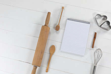Top view of a composition with an empty page in notebook with cookie cutters, whisker and rolling pin, arranged on on a white textured wooden surface 版權商用圖片