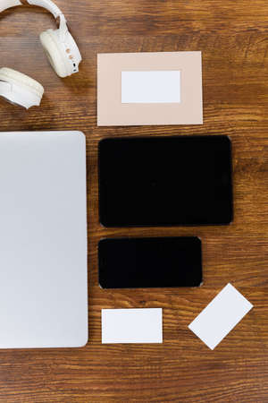 Close up top view of a laptop, a tablet, a smartphone, headphones and sheets of paper in various sizes arranged on a textured wooden surface 版權商用圖片