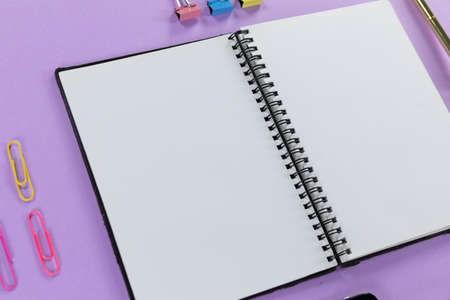 Close up top view of an empty page in a notebook and colorful paperclips arranged on a plain purple background