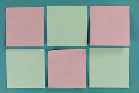 Close up top view of six green and pink sheets of paper sticky memo notes in one size, arranged on a plain blue background