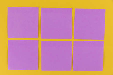 Close up top view of six purple sheets of paper sticky memo notes in one size, arranged on a plain yellow background 版權商用圖片