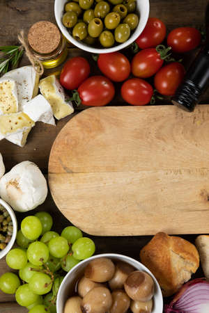 Top view of a wooden cutting board with pieces of bread, cheese, sausage, fresh fruits and a bottle of wine, arranged on a on a textured wooden surface.
