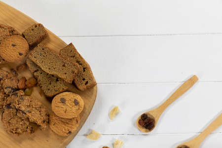 Top view of some cookies put on a wooden cutting board, arranged on on a textured wooden surface with two spoons with dried fruits.