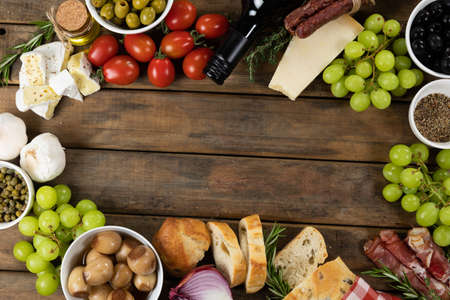 Top view of a composition with pieces of bread, cheese, sausage, fresh fruits and a bottle of wine, arranged on a on a textured wooden surface.