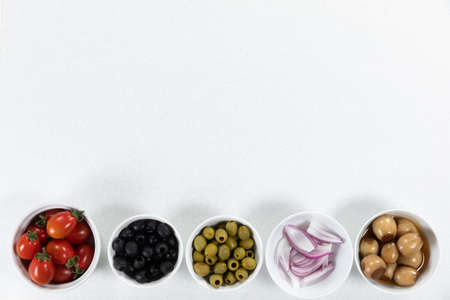 Top view of a six bowls with fresh tomatoes, olives, onion, nuts and seasoning, arranged on a on a plain white surface. 版權商用圖片