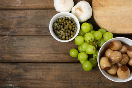 Top view of a wooden cutting board with bowls of snacks, some garlic and a bunch of grapes, arranged on a on a textured wooden surface.