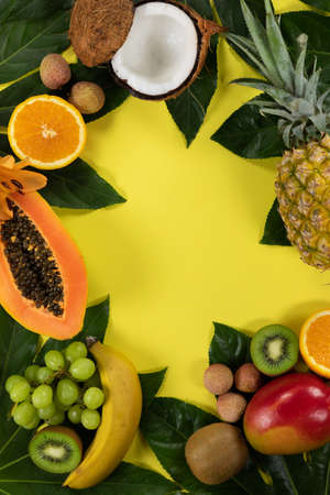 Top view of a composition with variety of fresh tropical fruits and green leafs arranged on a yellow surface. 版權商用圖片