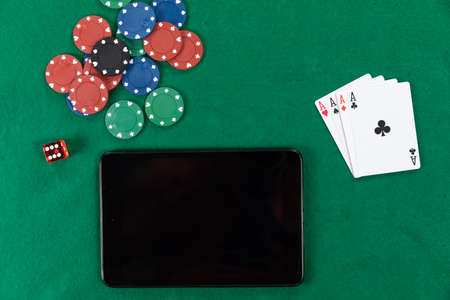 Close up top view of a black tablet, playing cards, a red dice and colorful poker chips, arranged on a plain green surface. 版權商用圖片