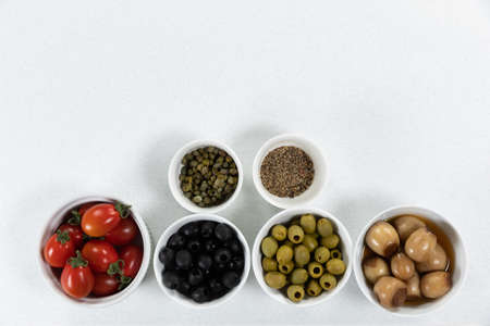 Top view of a six bowls with fresh tomatoes, olives, nuts and seasoning, arranged on a on a plain white surface.