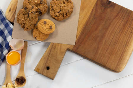 Top view of some cookies and ingredients prepared for baking, put on a wooden cutting board, arranged on on a textured white wooden surface with checkered tablecloth. 版權商用圖片