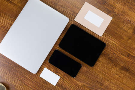 Close up top view of a laptop, a tablet, a smartphone and sheets of paper in various sizes arranged on a textured wooden surface