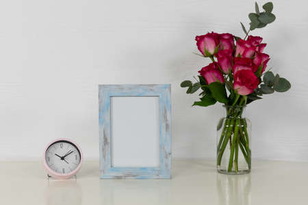 Close up view of an empty picture frame and a clock, with pink roses placed in a glass vase arranged on a plain white background