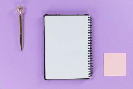 Close up top view of a notebook a pen and a small pink sheet of paper arranged on a plain purple background