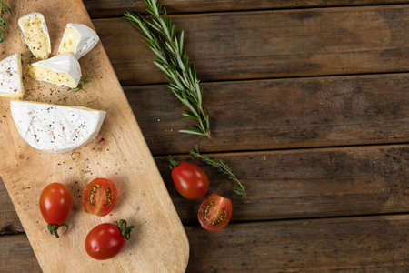 Top view of a wooden cutting board with cherry tomatoes and cheese arranged on a on a textured wooden surface with a spring of thyme.
