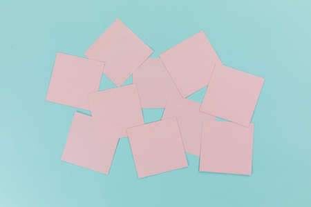 Close up top view of ten pink sheets of paper sticky memo notes in one size, arranged on a plain blue background