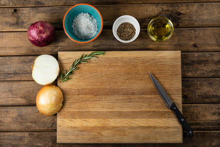 Top view of a wooden cutting board and knife with onion and seasonings arranged on a on a textured wooden surface with a spring of thyme.