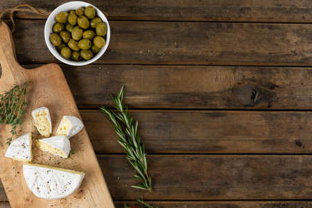 Top view of a wooden cutting board with cheese arranged on a on a textured wooden surface with a spring of thyme and a bowl of green olives. 版權商用圖片
