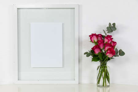 Close up view of an empty picture frame, with pink roses placed in a glass vase arranged on a plain white background