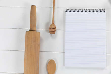Top view of a composition with an empty page in notebook with wooden spoon and rolling pin, arranged on on a white textured wooden surface