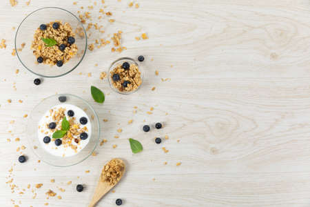 Top view of three bowls with muesli, nuts, blueberries and yoghurt, arranged on a textured white wooden surface. 版權商用圖片