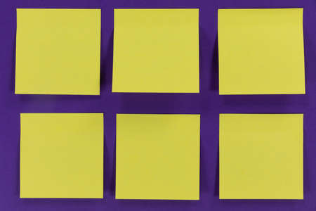 Close up top view of six yellow paper sticky memo notes in one size, arranged on a plain purple background 版權商用圖片
