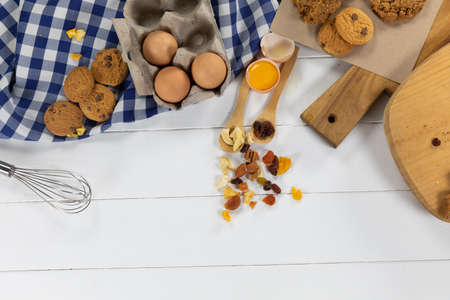 Top view of some cookies, spoons with dried fruits and eggs, arranged on on a textured white wooden surface with checkered tablecloth.