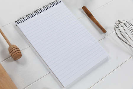 Top view of a composition with an empty page in notebook with wooden spoon and whisker, arranged on on a white textured wooden surface