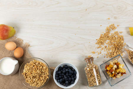 Top view of a variety of nuts and muesli, bowls of dried and fresh fruits and eggs, arranged on a textured wooden surface.