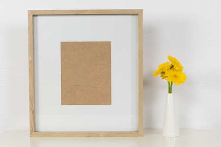 Close up view of an empty picture frame, with yellow flowers placed in a white vase arranged on a plain white background