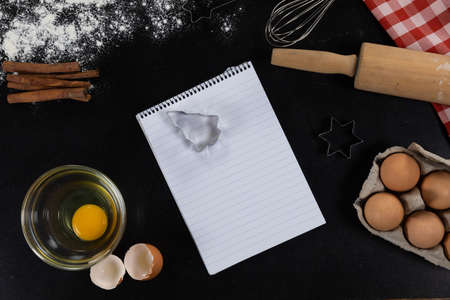 Top view of an empty notebook page with ingredients prepared for baking cookies, arranged on a plain black surface.
