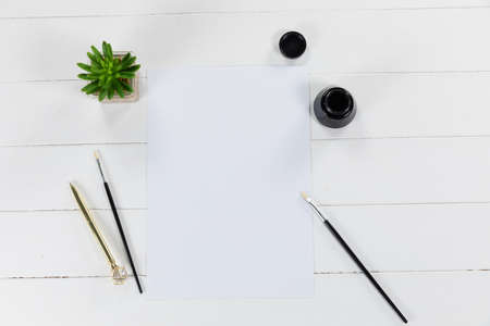 Top view of a white sheet of paper, a bottle of black ink and brushes with a green plant arranged on a plain white background